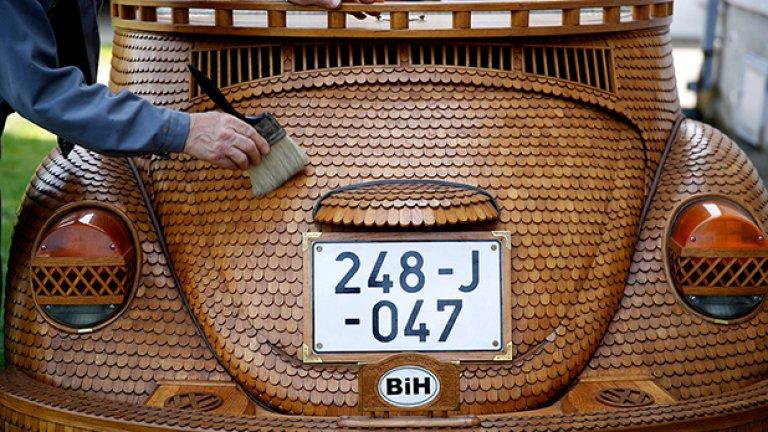 Божиц почиства дървения си автомобил пред дома си