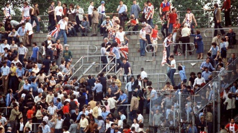 """Повече бой, по-малко футбол Евро `80 в Италия е първият континентален шампионат с групова фаза. В него Англия стартира с равенство 1:1 срещу Белгия в мач, който остава в историята с побоищата по трибуните на стадион """"Комунале"""" в Торино между хулиганите от Острова и италианските тифози. Мечтите за първото място в групата, водещо до финала, се изпаряват след загубата от Италия с 0:1 след късния гол на Марко Тардели. Победата с 2:1 над Испания в последния двубой не стига за нищо повече от трето място и стягане на куфарите за обратния път към Лондон."""