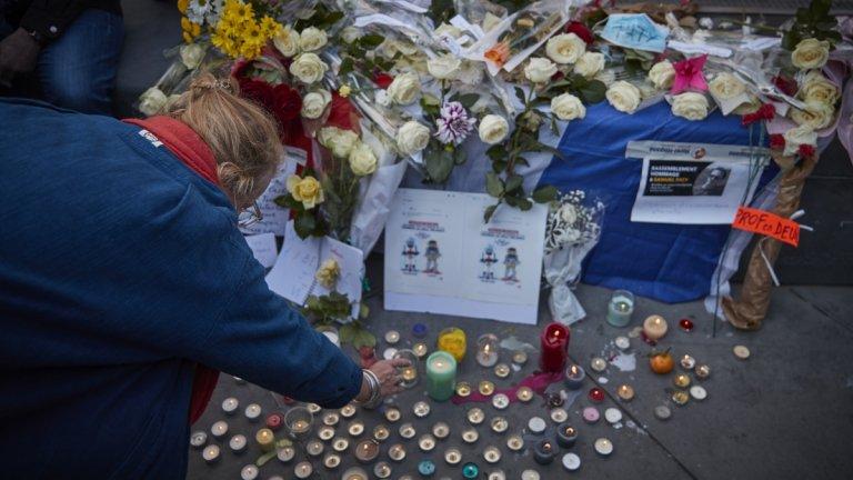Жена пали свещ в памет на убития учител. Хиляди се събраха на шествия във Франция в защита на свободата на словото.