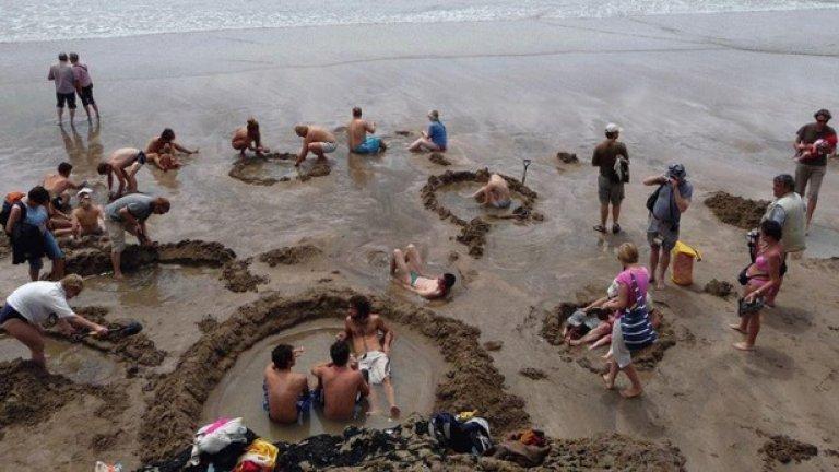 Посетителите на този новозеландски плаж се възползват от топлите извори, които проникват през пясъка, и често си изравят големи дупки, за да се поплицикат в горещите води