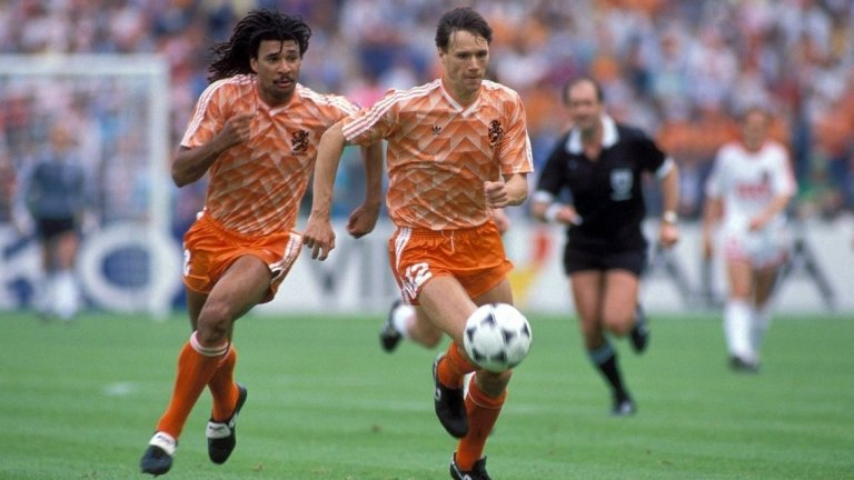 """Холандия, Мондиал 1986 След Мондиал 1978 холандскяит футбол преживява трансформация, като пропуска Мондиал 1982 и дори Евро 1984 (второто заради изключителен успех на Испания с 12-1 срещу Малта, който класира иберийците в последния мач от групите). Но по време на квалификациите за Мондиал 1986 вече се е появило следващото силно поколение холандски футболисти. В състава на """"лалетата"""" блестят имената на Гулит, Рийкард и Ван Бастен, които са наследили тоталния футбол в Аякс под ръководството на Йохан Кройф. До голяма степен неуспехът на тима е свързан със смяната на трима различни треньори в хода на шестте квалификационни мача. Първият мач е загубен от Рийс Райверс срещу Унгария, след което на пожар е привикан Ринус Михелс, но отборът губи отново (с 1:0 от Австрия). Тогава начело застава Лео Бенхакер, но тима стига само до плейофите. Там """"лалетата"""" се изправят срещу Белгия, където губят с 1:0 след гола на Веркаутерен и губят за реванша Вим Кийф (червен картон) и Марко Ван Бастен (натрупани жълти картони). Дори тогава """"оранжевите"""" повеждат с 2:0, но 5 минути преди края Жорж Грюн праща Белгия на Мондиала."""