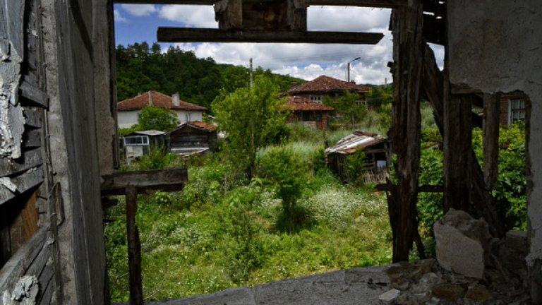 От липсващите стени на кметството се открива гледка към останалите къщи в селото. Много от тях - също изоставени.