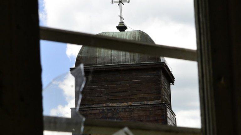 Камбанарията на местната църква наднича през изпочупените стъкла на един от прозорците.