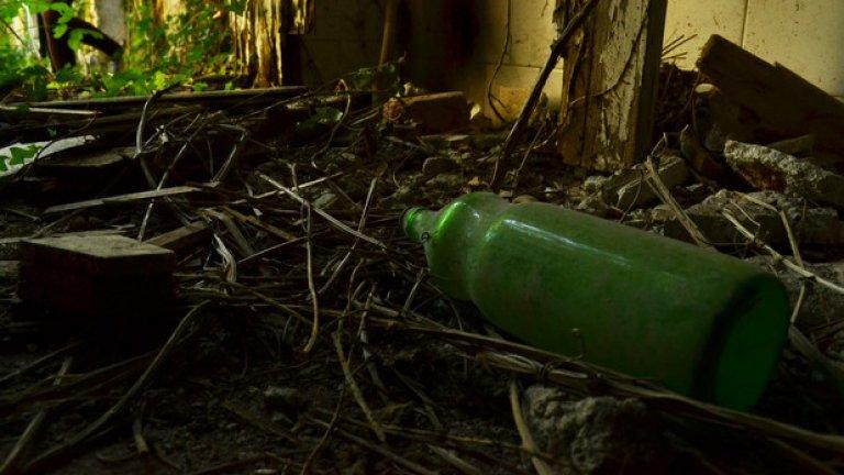 Стъклена бутилка от олио от близкото минало лежи върху влажния под на банята