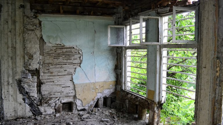 Текст: Кирпичената мазилка се руши и оголва следите от някогашен ремонт  - дървесината на част от стената е заменена с цимент.
