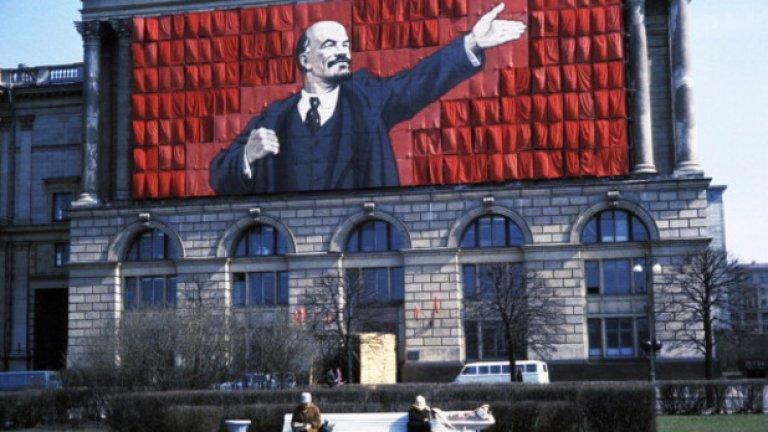 Седем съвета за диктатори от ерата на СССР  Снимка: Плакат на Ленин опънат върху обществена сграда и две възрастни жени, седнали в парка отпред, Ленинград, СССР, 60-те години/ Getty Images