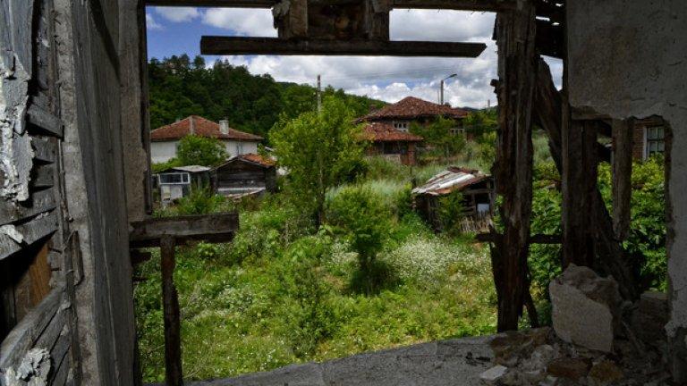 Останките от рухналата стена тъжно гледат към обитаемите къщи в съседство.