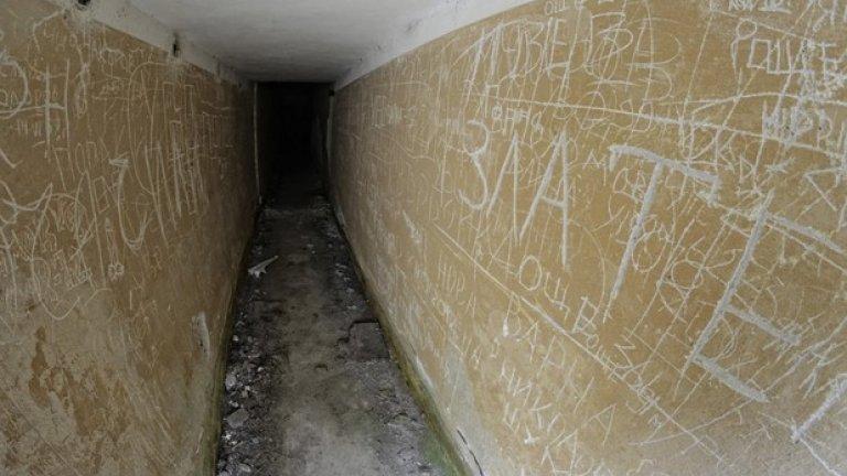 Тесен коридор отвежда към вътрешността на бункера. По стените личат надписи, оставени от отдавна служили войници