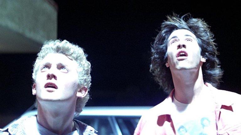 """""""Чудесното приключение на Бил и Тед"""" (Bill and Ted's Excellent Adventure)Година:1989Всъщност поводът за галерията беше тъкмо новината, че близо 30 години след първото """"отлично"""" приключение на героите на Киану Рийвс и Алекс Уинтър, през август предстои да излезе и трети филм от франчайза.  Нека обаче се върнем в 1989 г., когато Рийвс е на 25 г., а Уинтър - на 24. Двамата тогава играят симпатични, но откровено наивни (дори леко глупави) гимназисти, които искат да основат своя хеви метъл банда. Уви, един изпит по история им пречи да осъществят мечтата си, но появата на неизвестен мъж от бъдещето им помага да се върнат в миналото и да се запознаят лично с личностите от учебниците."""