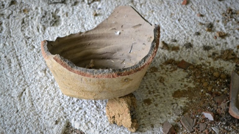 Останките от някогашни глинени съдове напомнят за миналото, когато сградата е била обитаема.