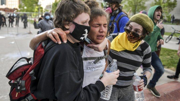 Жена, получава помощ от протестиращи, след като е била напръскана с лютив спрей по време на протеста в Денвър.