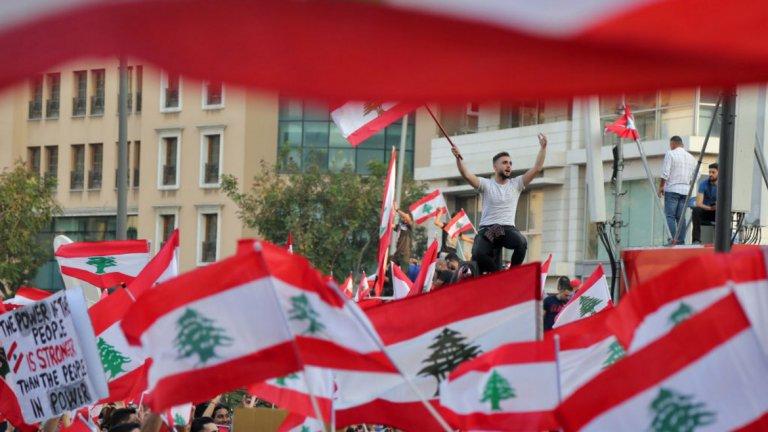 """Ливан  Кой протестира там и защо?  Протестиращите в Ливан са от различни общности, религии и политически групи. Сред протестиращите могат да се видят стари, млади, религиозни и нерелигиозни, като всички застават заедно срещу политическа система, която според тях е прогнила и корумпирана. Какво предизвика протестите и кога те започнаха?  Безпрецедентната вълна от демонстрации в Ливан има дълбоки корени заради корупцията и растящите социални пропасти. Мнозина обаче посочват като конкретен повод за протестите обявения от правителството """"данък WhatsApp"""" като последната капка, след която чашата е преляла. Други твърдят, че бездействието на правителството по отношение на пожарите, които разкъсаха страната през последния месец, е също причина за протестите."""