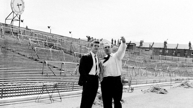"""Мениджърът на Арсенал Били Райт развежда новото попълнение Джо Бейкър из """"Хайбъри"""" през 1962-а. По-късно двамата очакват телефонно обаждане от Торино, с което окончателно да бъде финализиран трансферът за 70 хил. паунда. (Вижте часовника на стадиона в дъното...)"""