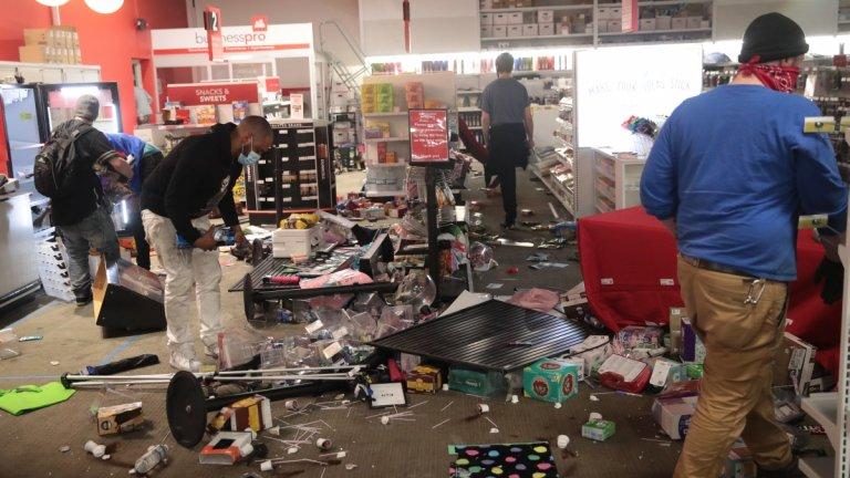 Хора обикалят из магазин, разбит по време на протестите в Минеаполис.