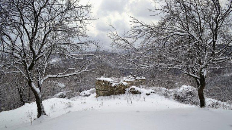 Две овощни дръвчета отбелязват мястото, където започва махалата. Побелелите от снега останки от първата къща едва се забелязват между тях.