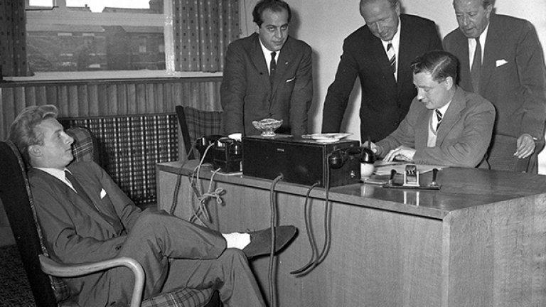 """Езикът на тялото на Денис Лоу казва: """"Дано това е всичко"""", докато гледа секретаря на Манчестър Юн., който дооформя договора му за преминаване от Торино при """"червените дяволи"""". На снимката се вижда и Мат Бъзби. През 1962-а Лоу преминава на """"Олд Трафърд"""" за 115 хил. паунда, като чупи с 15 хил. собствения си рекорд - 100 хил., които Торино плаща на Манчестър Сити година по-рано. Легендарният шотландец прекарва 11 години в Юнайтед, като помага на тима за титлите през 1965-а и 1967-а и за спечелването на КЕШ следващата година. За онова поколение фенове на """"червените дяволи"""" той беше просто Кралят."""