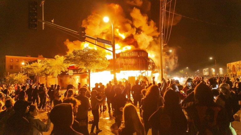 Протестиращи стоят пред запален магазин в Минеаполис.