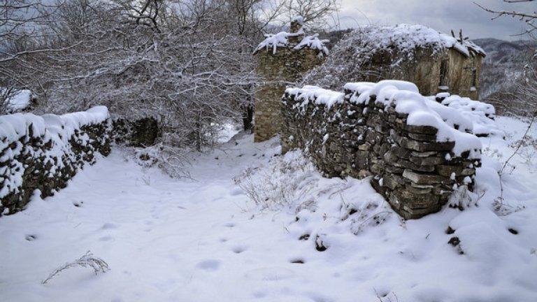 Снегът е покрил главната уличка на махалата. Следите от лапи показват, че дивите животни са единствените живи същества, които минават оттук.
