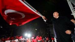Мевлют Чавушоглу на сцената на резиденцията в Хамбург, развява турския флаг
