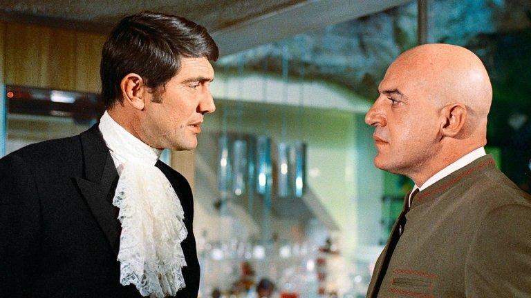 """""""В служба на Нейно величество"""" (On Her Majesty's Secret Service, 1969 г.) Бонд е: Джордж Лейзънби  Нещо свежо, нещо различно, нещо... с халка? Филмът ще ви предложи един различен Бонд, който така и няма да откриете в другите. Тук обект на любовния интерес на 007 е прелестната Даяна Риг в ролята на италианска контеса, а завоеванията отстъпват място на истинска любов.  Тук Бонд вече знае кой е начело на СПЕКТЪР и търси лидера му, но така се озовава в необичайна ситуация - спасява жена, която планира да се самоубие. Това тласка шпионина в правилната посока и към поредната конспирация, този път свързана с проминване на мозъци и... бактериологична заплаха."""