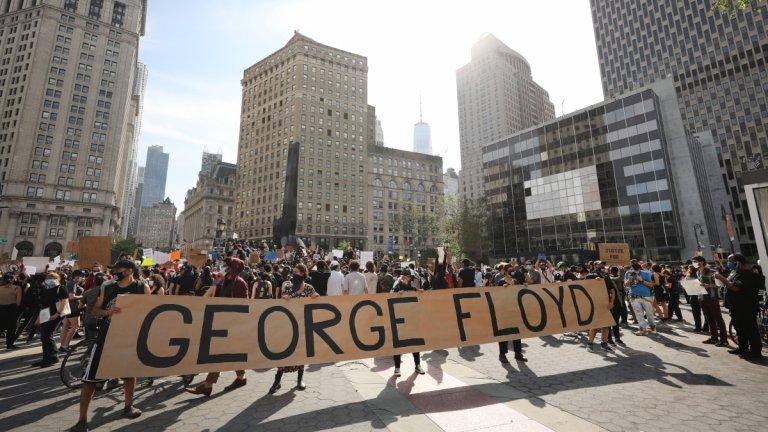 Протестиращи носят транспарант с името на загиналия Джордж Флойд по време на протест в Манхатън, Ню Йорк.