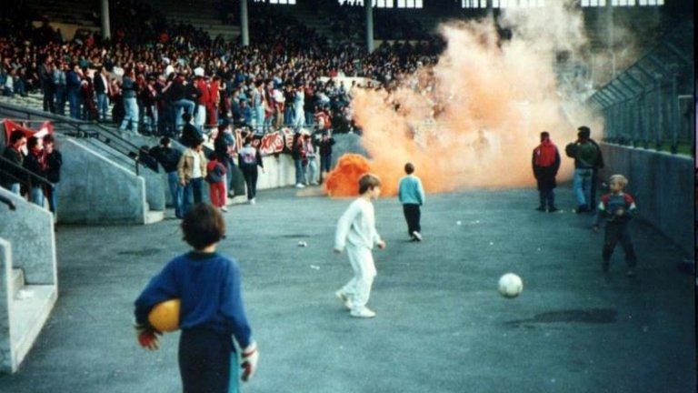 Деца играят с топки зад загражденията в един от секторите, а около тях се мятат факли, димки и бомбички по време на сблъсък между Тулуза и Ница в края на 80-те.