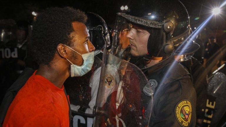 Протестиращ лице в лице с полицай по време на демонстрациите в столицата Вашингтон.