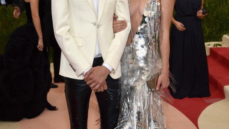 """Моделът Лъки Блу Смит привлече погледите в тесен светъл смокинг от италианска вълна с подчертани рамене, комбиниран с бяла копринена риза с копчета Swarovski. Визията му бе допълнена от кожени панталони със синьо покритие в цвят металик.    Неговата сестра, моделът Пайпър Америка Смит, бе истинско видение в сребриста ефирна рокля, съчетаваща машинни и ръчни техники на изработка, с лазерно изрязани пера от винил и ресни, ръчно пришити към основа от копринен тюл и корсет с пайети.   """"Чувствам се истинска късметлийка, че имах възможността да работя с H&M за моя първи Мет Бал! Роклята ми е перфектен пример за темата на събитието тази година, съчетавайки сложни детайли и иновативни текстилни технологии без да се прави компромис с емблематичния силует"""", сподели моделът Пайпър Америка Смит."""
