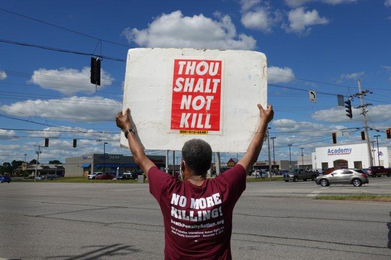 Мъж протестира срещу смъртното наказание в деня на екзакуцията на Лий.