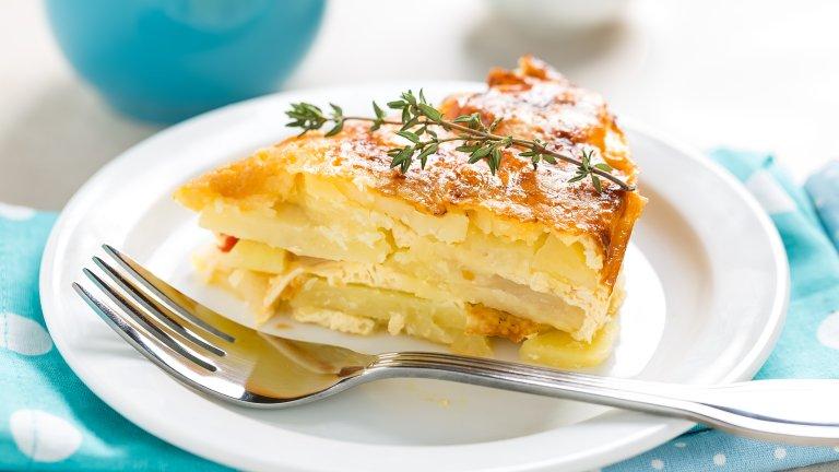 """Картофи """"Дафиноаз""""Или по-изтънчената версия на огретена, която всъщност се прави далеч не толкова трудно и изтънчено. Тук най-времеемката задача е да нарежете седем или осем големи картофа на много тънки филийки - не повече от 3-4 милиметра. Докато резените картоф си почиват в купа студена вода, загрейте на котлона в дълбока тенджера 500 мл. сметана и 500 мл. прясно мляко с няколко накълцани скилидки чесън, сол и пипер.   Когато сместа започне да къкри, изсипете в нея картофите и разбъркайте около три минути, за да се отделят резените. Извадете картофите с решетъчна лъжица и ги наредете на пластове в огнеупорна тава. Заливате с млечната смес и печете на 180 градуса за 30 минути.   Вадите от фурната, ръсите с настъргано сирене гюер и запичате за още 5 минути до златиста коричка."""