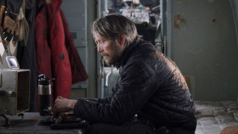 """9. Arctic  Тих и грабващ приключенски филм с участието на Мадс Микелсен. Тук той играе изследовател, който е изгубен в замръзналата пустош. Филмът е първият проект на бразилския режисьор Джо Пеня. """"Arctic"""" е история за оцеляването, в която няма кратки пътища или избождащи очите действия, възможни само във филмите. Главният герой не може да разчита на почти нищо освен своята воля, което помага на зрителя да се почувства на негово място. Филмът е изграден около грубата мистичност на Микелсен, чиято игра никога не включва дори намек за фукане. Той изпълва кадъра с присъствието си, а лицето му винаги показва напрегнатост и фокус."""