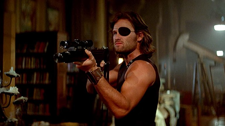 """Escape From New York/Бягство от Ню Йорк  Помните ли го Кърт Ръсел?  Последните години се позагуби, но през 80-те и началото на 90-те той е една от най-горещите екшън звезди на Холивуд. Кариерата му започва далеч преди това, още като тийнейджър, но истинският му пробив идва с нискобюджетния футуристичен """"Бягство от Ню Йорк"""". Той става толкова успешен, че много хора и до днес свързват превръзката за очи със Снейк Плискин, а не с еднооките пирати.  Историята е класически постакалиптичен разказ за тогавашното бъдеще през 1997 г, когато остров Манхатън е превърнат в гигантски затвор за най-ужасните престъпници. Американският президент е похитен, а единственият човек, който може да го освободи е Снейк Плискин."""