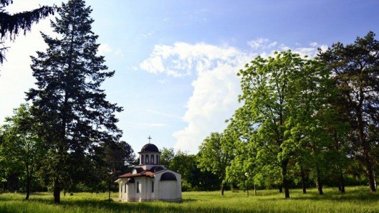 Лишен от медния блясък на купола си, малкият параклис се е сгушил сред зеленината на дърветата.