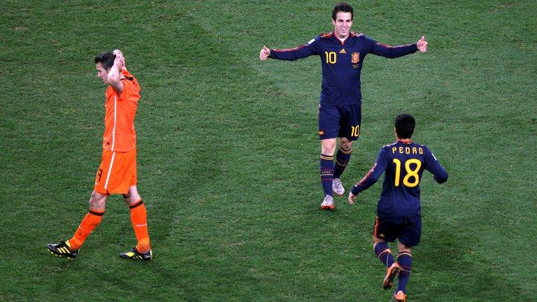 Сеск Фабрегас (Испания) ликува след спечелената световна титла през 2010 г., докато съотборникът му в Арсенал тогава Робин ван Перси (Нидерландия) е потънал в мъка.