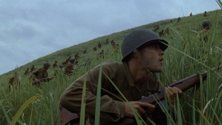 """""""Тънка червена линия""""   Философският епос на Терънс Малик за Втората световна война е един от най-елегантните филми по темата и визуално откровение на неговата дистанцирана естетика. Произведението ни отвежда из красивите острови в Тихия океан. Зеленото на военните машини се влива в зеленото на джунглите."""