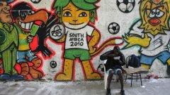 """Жител на квартал """"Вила Изабел"""" в Рио де Жанейро обядва на улицата, украсена с графити по случай световното първенство по футбол в Южна Африка"""