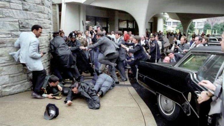 """6. Роналд Рейгън (президент на САЩ в периода 1981-1989 г.)  На 30 март 1981 г. Роналд Рейгън излиза от хотела """"Хилтън"""" във Вашингтон, когато срещу него е открит огън. Той и трима други са ранени. Американският президент е улучен от един куршум, който чупи едно от ребрата му и пробива белия му дроб. Въпреки това Рейгън се възстановява бързо. Ранени са и говорителят на Белия дом, един охранител от """"Сикрет сървис"""" и един полицай. Всички оцеляват, но прессекретарят Джеймс Брейди получава увреждане на мозъка и остава инвалид до края на дните си.  Стрелецът - Джон Хинкли-младши, има странен мотив - целта на нападението е да впечатли актрисата Джоди Фостър, която той е гледал в излезлия няколко години по-рано филм """"Шофьор на такси"""". По време на съдебния процес той е оневинен, тъй като е определен от съда за невменяем. Хинкли е вкаран в психиатрична клиника, в която остава до 2016 г., когато е освободен."""