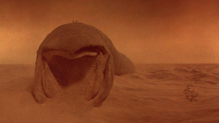 """Пясъчният червей от """"Дюн"""" беше сред най-чаканите образи в новия филм на Дени Вилньов по романа на Франк Хърбърт, който трябваше да излезе през 2020 г., но бе отложен заради пандемията. Първата екранизация на романа е на Дейвид Линч е от 1984 г. и там също могат да бъдат видени гигантските същества. Пясъчните червеи властват на пустинната планета Аракис и са много, ама много големи. Именно техните ларви произвеждат подправката меланж, която е ключова в плановете на човечеството."""