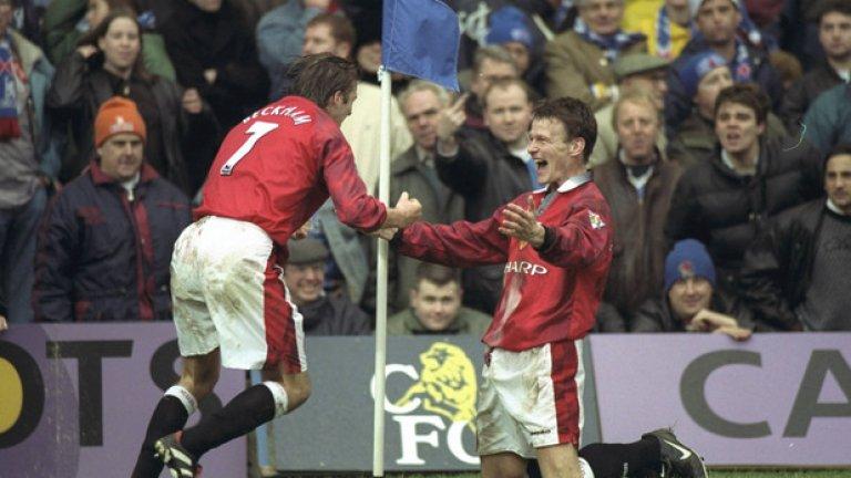 """1996/97 и 1997/98 Титулярният екип Червеното винаги е на мода. Този път се появява дори и на гащетата. Сивите якички и черното в края на ръкавите обаче бодяха очите на феновете два поредни сезона. Ерик Кантона изигра последния си мач за """"червените дяволи"""" с този екип – през октомври 1997 г. срещу Уест Хем на """"Олд Трафорд""""."""
