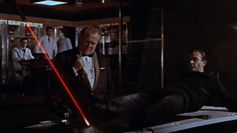 """Аурик Голдфингър  """"Голдфингър"""" е един от най-запомнящите се филми от поредицата и абсолютна класика. За това немалка роля има и главният злодей, представен от немския актьор Герт Фрьобе. Целта му е да взриви ядрена бомба във """"Форт Нокс"""". По този начин иска да унищожи американския златен резерв и реално да направи безценен своя собствен запас.   Напълно луд и вманиачен по златото, Голдфингър остава известен с фразата си """"Не, господин Бонд, очаквам да умрете"""", докато се опитва да разполови с лазер тайния агент."""