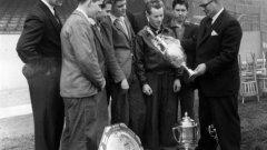 Мениджърът на Арсенал Том Уитъкър показва на юноши купите, които клубът е печелил