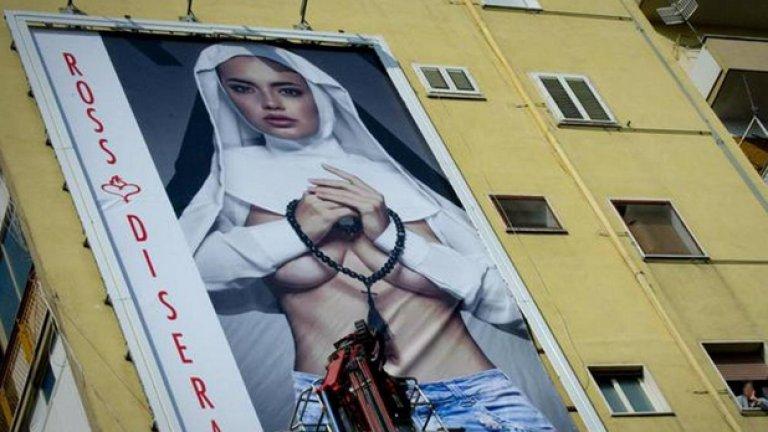 """Изображението на полуголата """"монахиня"""" в размер 6 х 9 метра предизвика гневна реакция от страна на религиозната общност, които я определят като """"порнография"""" и """"богохулство""""."""