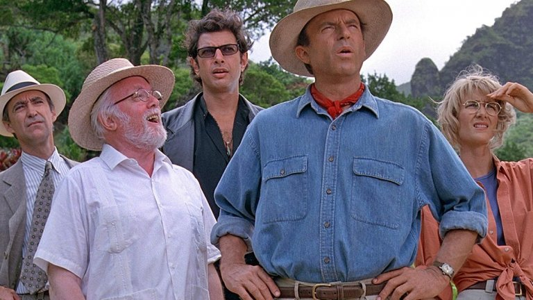 """Сам Нийл като проф. Алън Грант в """"Джурасик свят 3""""  Най-запомнящият се персонаж от поредицата """"Джурасик парк"""" (освен самите динозаври) е проф. Алън Грант - палеонтологът, който доживява мига да види скелетите, които е откривал, като ходещи, дишащи и гладни създания. Това без съмнение е и най-популярната роля на актьора Сам Нийл (на снимката: със синята риза), когото можете да видите в страхотна форма и в първия сезон на сериала Peaky Blinders. За радост на феновете на поредицата, Нийл ще се завърне като Грант в третия филм от новата трилогия за динозаврите, който за момента носи работното заглавие """"Джурасик свят 3"""". Лошата новина? Ще трябва да почакаме до следващото лято за неговото завръщане.  Премиера: 11 юни 2021 г."""