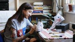 Тя е художник с шарени татуировки и огромна усмивка.