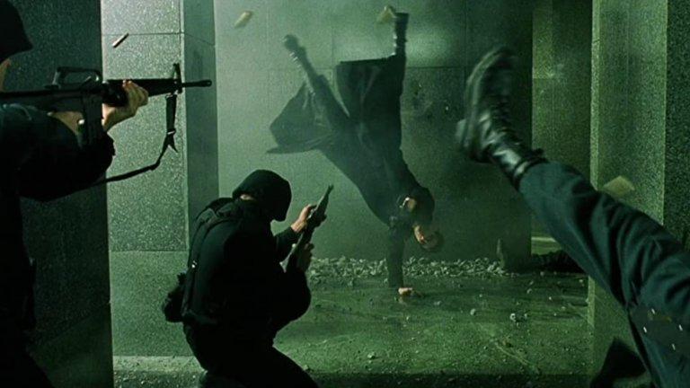 """""""Матрицата"""" - Престрелката във фоайето  """"Матрицата"""" е толкова революционен и запомнящ се филм, че практически всеки един момент от него е велик сам по себе си. Това важи особено много за екшън сцените, които правят истинска революция в киното заради въвеждането на цял куп нови визуални ефекти.  Един от запомнящите се моменти, освен ръкопашните схватки, е престрелката във фоайето на бизнес сградата, когато Нео и Тринити отиват да спасят Морфей от плен. В нито един момент двамата не изглежда да бъдат в опасност, а целият акцент е поставен върху абсолютното им превъзходство над охраната на фона на пороя от олово и падащи отломки. Всичко това е заснето с няколко подхода на забавения кадър, които после започват да бъдат широко прилагани и в други филми."""
