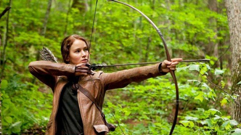 """The Hunger Games   Първата част на """"Игрите на глада"""" носи голямата световна слава на актрисата, както и обожанието на тийнейджърите. Базирани на романите на Сюзън Колинс, филмите пренасят зрителя в антиутопично бъдеще, в което деца биват изпращани на арена, за да се бият до смърт – за назидание на масите и забавление на богатите.   Лорънс влиза в кожата на силната и опърничава Катнис Евърдийн, която заема мястото на малката си сестра и я спасява от почти сигурна смърт в битката. Мнозина критикуват избора на Дженифър за главната роля, но яростта, с която на екрана тя защитава себе си и близките си, кара критиците да замлъкнат."""