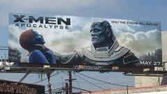 Спорният билборд показва как злодеят Апокалипсис (Оскар Айзък) упражнява насилие върху Мистик (Дженифър Лорънс)