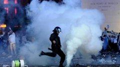 Полицай изритва димка, хвърлена от ултрасите.