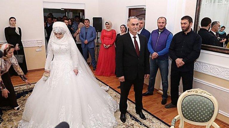 Луиза Гойлабиева стои на разстояние от бъдещия си съпруг Нажуд Гучигов. Младата жена едва не припадна в ритуалната зала.