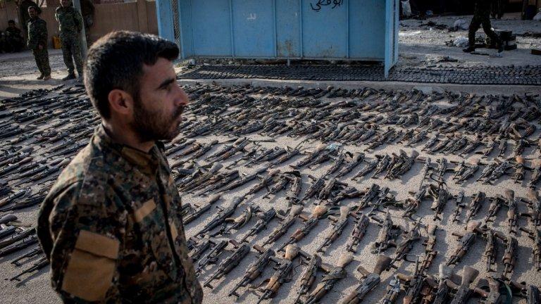 """Войник на Сирийските демократични сили (SDF) пред иззето от """"Ислямска държава"""" оръжие в Бангуз, Сирия."""